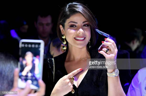Morrocan actressmodel Leila Hadioui poses for a photo with a Samsung Galaxy Z Flip phone display during the Samsung Galaxy Unpacked 2020 event in San...