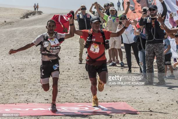 Morrocan trail runner Rachid El Morabity and Peruvian Remigio Huaman Quispe cross the finish line to win the 6th and last stage of the first edition...