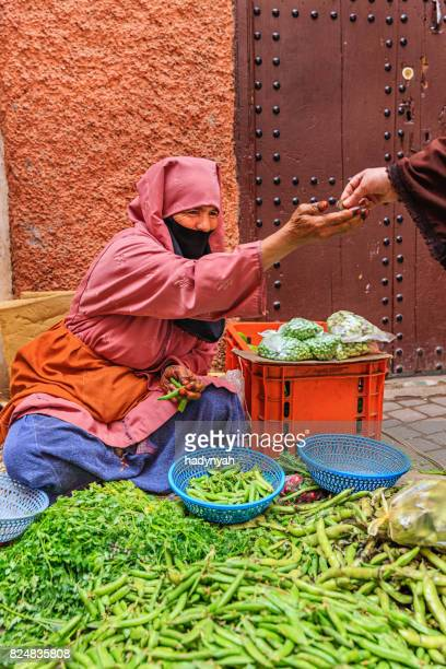 morrocan woman selling vegetables on street market, marrakech - djemma el fna square stock photos and pictures