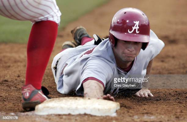 Morrow Thomley of the University of Alabama dives back to first base around Jefferies Tatford of University of Louisiana Lafayette during the 8th...