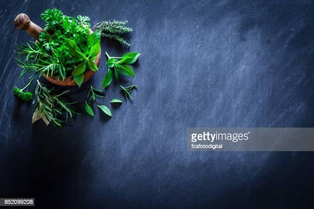Murbruk och pastle med färska örter för matlagning på mörka köksbord