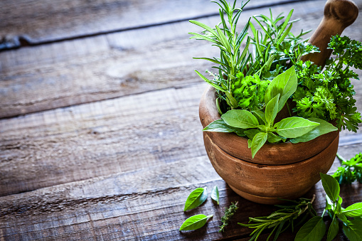 Mortar and pastle with fresh herbs for cooking on rustic wooden table 852094214