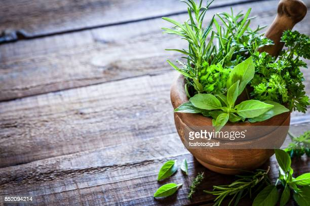 Mortar and pastle with fresh herbs for cooking on rustic wooden table