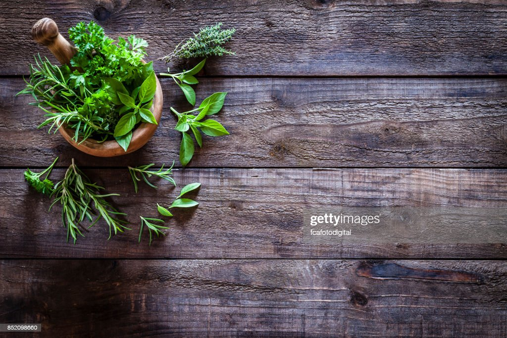 Mortar and pastle with fresh herbs for cooking on rustic wooden table : Stock Photo