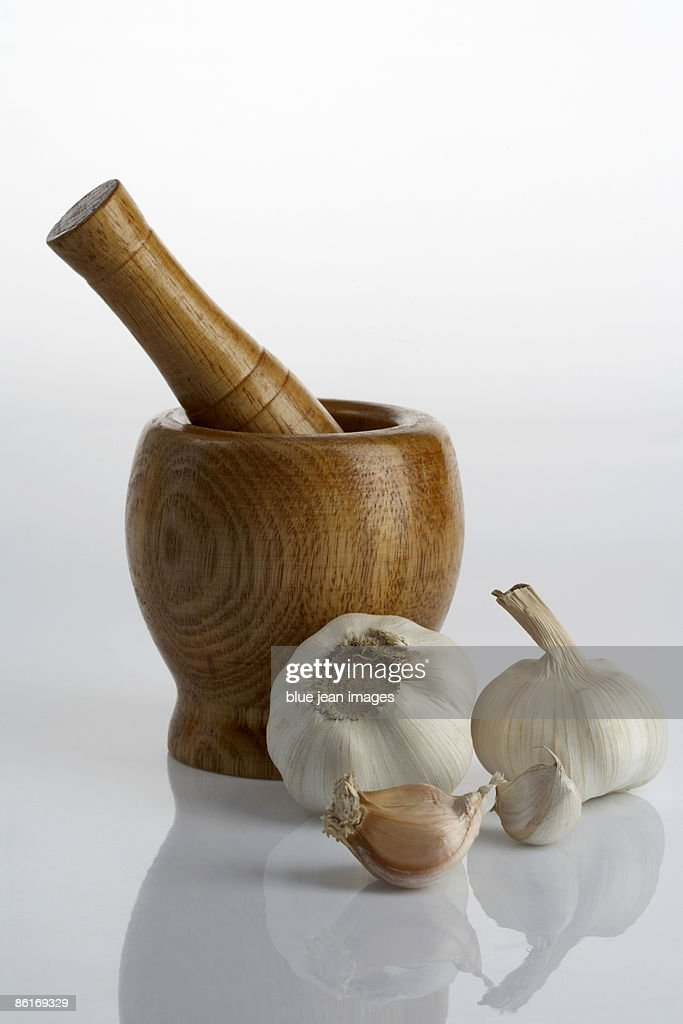 A mortar and pestle with cloves and bulbs of garlic : ストックフォト