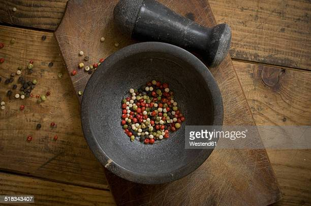 mortar with dried green, red, white and black peppercorns on wood, elevated view - pfeffer stock-fotos und bilder