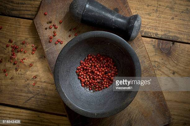 Mortar with dried red peppercorns on wood, elevated view