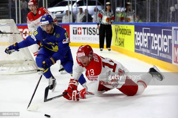 Morten Green of Denmark challenges Elias Lindholm of Sweden for the puck during the 2017 IIHF Ice Hockey World Championship game between Denmark and...