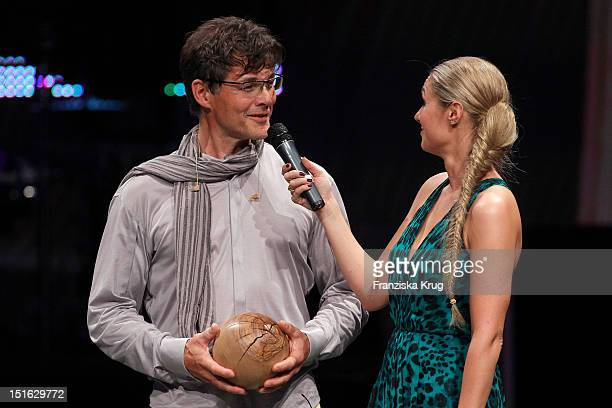 Morten Harket receives the Clean Tech Media Award from Ruth Moschner during the Clean Tech Media Award ceremony at Tempodrom on September 7 2012 in...