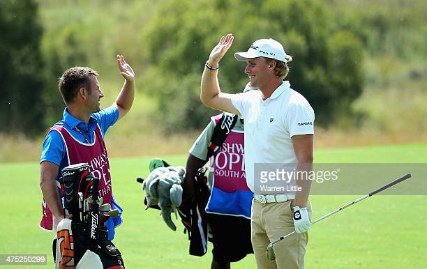 Morten Orum Madsen of Denmark celebrates with his caddie after making an eagle on the seventh hole during the first round of the Tshwane Open at...