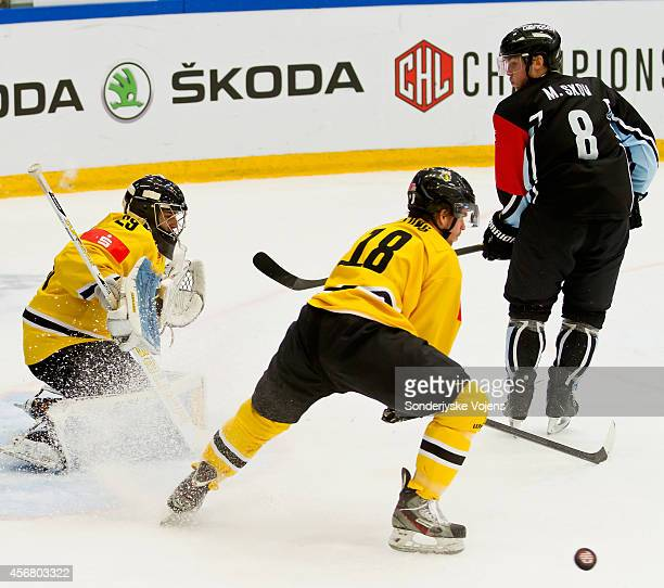 Morten Skov of Vojens loses control of the puck against Colin Long and Patrick Klein of Krefeld Pinguine during the Champions Hockey League group...