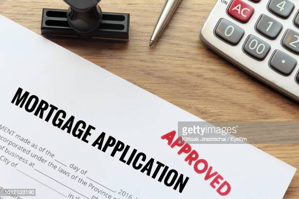 mortgage application from by calculator on table - mortgage stock pictures, royalty-free photos & images