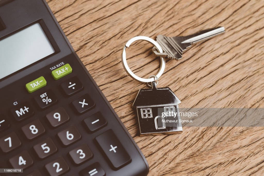 Mortgage calculation or buy and sell house, property and real estate, home key with house keyring or keychain with black calculator on wooden table : Stock Photo