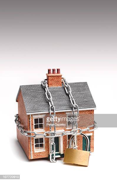 Mortgaged house in padlock and chains