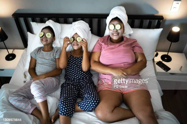 morther and daughters in bed doing skin care with cucumber slices over the eyes - sunday stock pictures, royalty-free photos & images
