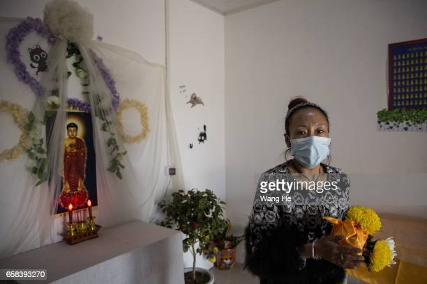 A mortician holds the casket of pet dog Xiaoxiao who died at the age of 6months on March 27 2017 in Wuhan Hubei province ChinaWangzai Pet Service...
