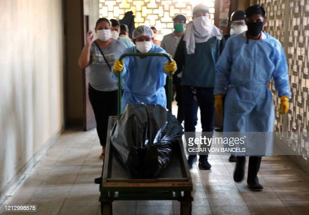 Mortuary crew transport the dead body of a victim of COVID-19 novel coronavirus pandemic at the regional hospital in Iquitos, the largest city in the...