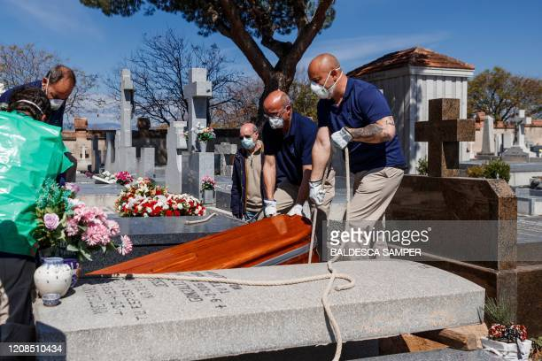 TOPSHOT Mortuary employees wearing face masks burry the coffin of a COVID19 coronavirus victim at Fuencarral cemetery in Madrid on March 29 2020...