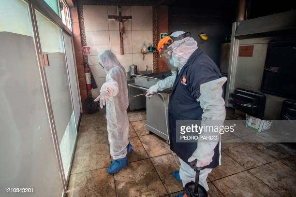 Mortuary workers disinfect each other after the cremation of the body of a COVID19 victim at a crematorium in Cuautitlan Izcalli Mexico State on...