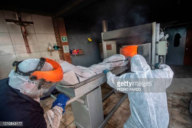 Mortuary workers load the body of a COVID-19 victim into a furnace at a crematorium in Cuautitlan Izcalli, Mexico State, on April 23, 2020. - By...