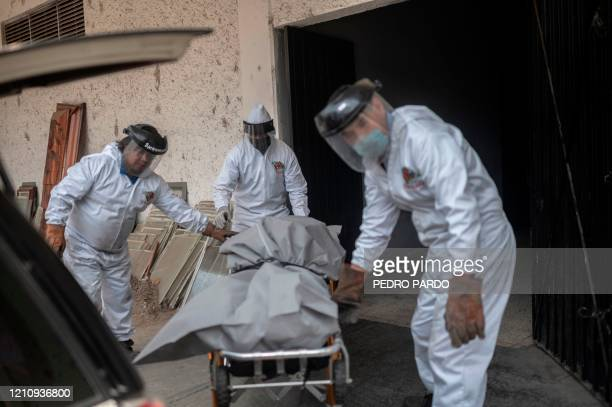 Mortuary workers move the body of a COVID-19 victim at a crematorium in the Iztapalapa neighborhood, in Mexico City, on April 24, 2020. - By...