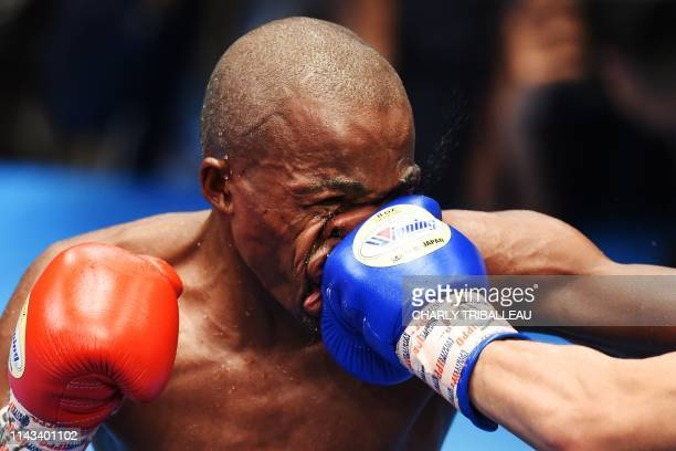 Moruti Mthalane of South Africa is punched by Masayuki Kuroda of Japan during their IBF flyweight title boxing bout in Tokyo on May 13, 2019.