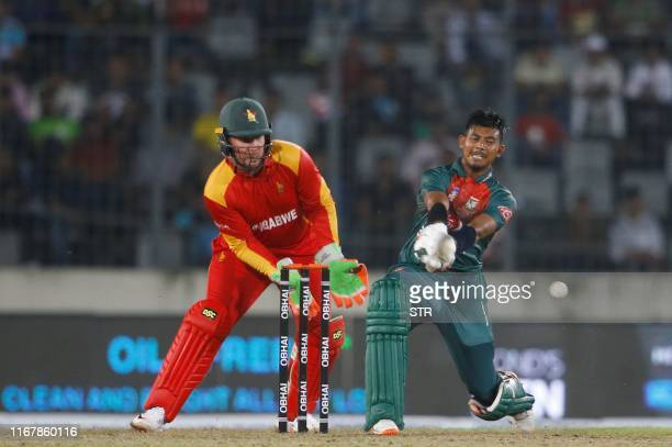 Mosaddek Hossain from Bangladesh plays a shot as the Zimbabew wicket keeper Brendan Taylor looks on during the first match between Bangladesh and...