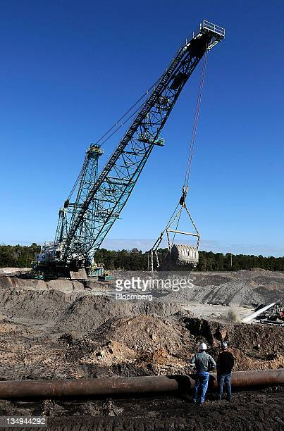 Mosaic Co workers watch a dragline dump phosphate matrix into a slurry pond in Tampa Florida US on Friday Dec 2 2011 Mosaic Co is the world's largest...