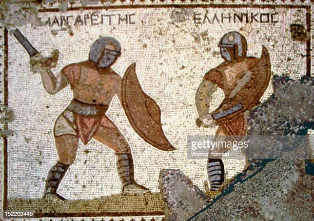 Mosaic from the House of the Gladiators Two gladiators enganged in a practice bout with blunt weapons Above their heads are their names in Greek...