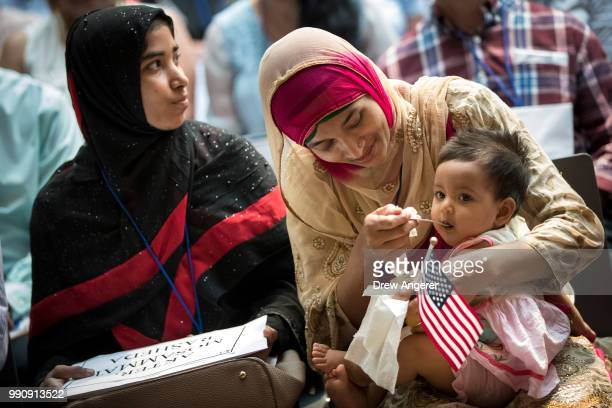 Mosammat Rasheda Akter from originally from Bangladesh feeds her 7 monthold daughter Fahmida before officially becoming a US citizen during a...