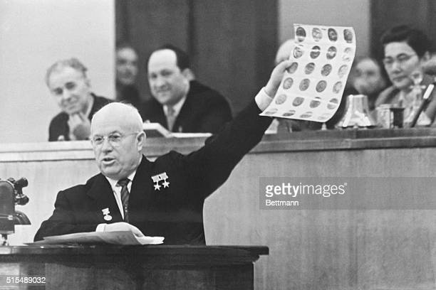 Appearing before the Soviet Parliament Soviet Premier Nikita Khrushchev holds aloft photos which he identified as views of Military and Industrial...