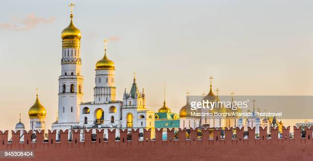 moscow kremlin, the walls and the onion golden domes of the ivan the great bell tower (really a church tower) on the left and, on the right, of the cathedral of the dormition - kremlin stock pictures, royalty-free photos & images