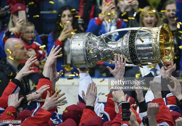 Moscow players hold the trophy as they celebrate their victory over Avangard Omsk after the Gagarin Cup 2019 final series game of the Russian...