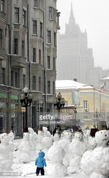 A child walks through snowmen installed at the Arbat a popular pedestrian shopping and entertainment street in Moscow 25 January 2006 Several dozen...