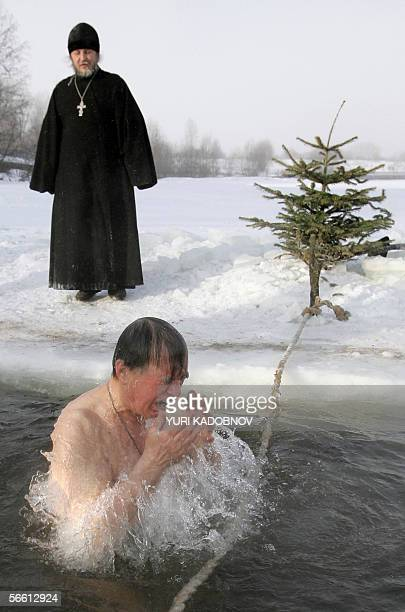A Russian Orthodox believer takes a lustration bath in the icy waters of the Moskva river during the celebrations of the Epiphany holiday during...