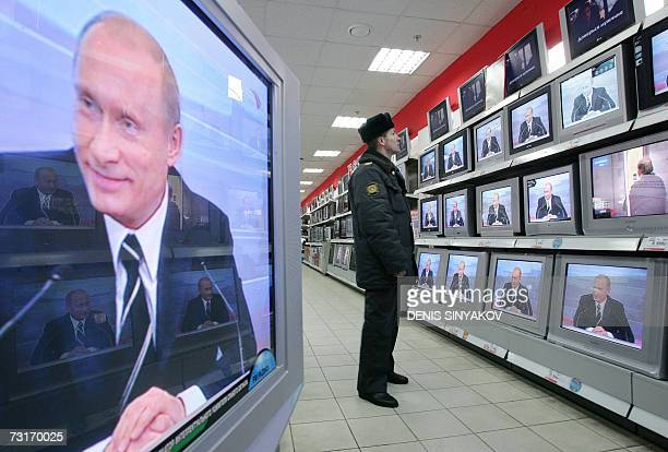 A Russian policeman looks at TV screens in a shop 01 February 2007 in Moscow during the broadcasting of Russian President Vladimir Putin's annual...