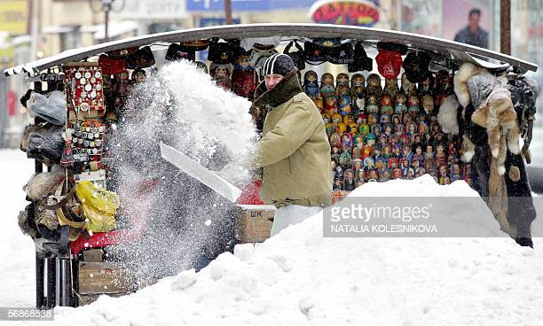A street vendor cleans snow in front of his stall with Russian souvenirs in Arbat a popular pedestrian shopping and entertainment street in Moscow 17...