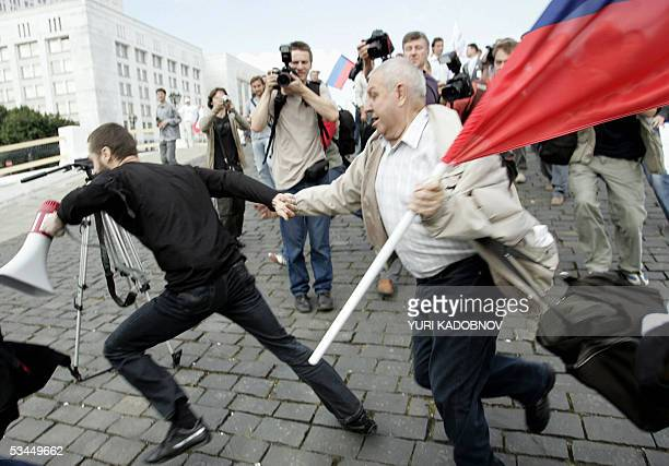 A supporter of the Union of Right Forces liberal political party holding the Russian flag tries to catch an escaping young leftist activist who...