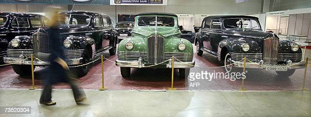 A woman passes by ZIS110 limousines used by Josef Stalin from a special purpose garage of FSB before the opening of retro cars exhibition in Moscow...