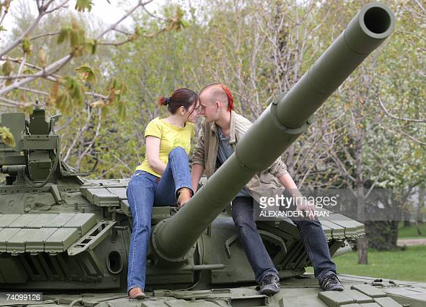 A young couple kiss as they sit on a tank turret at a memorial to WW II at Poklonnaya hill in Moscow 08 May 2007 Russia celebrates the Victory Day...