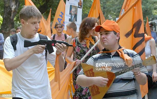 A youth aims a toy rifle as another one plays balalaika during a rally held near the Russian Defence Ministry in Moscow 11 June 2005 They protested...