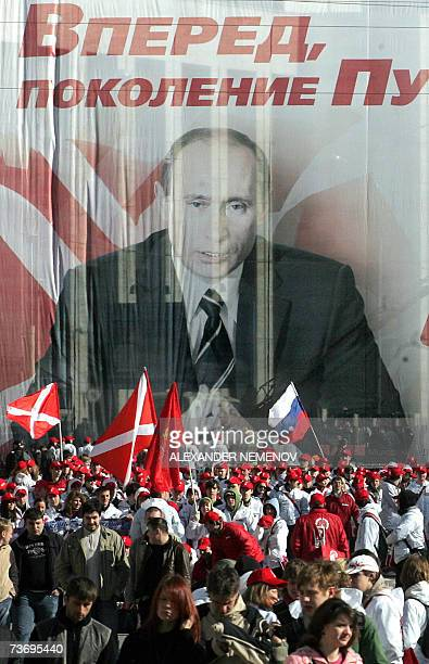 Activists of proKremlin Nashi youth movement march in front of a huge poster of Russian President Putin reading Go Putin's Generation in downtown...
