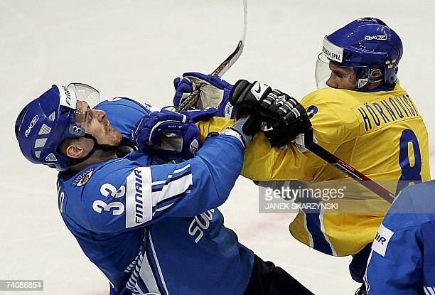 Moscow, RUSSIAN FEDERATION: Finnish Pekka Saravo fights with Swedish Patric Hornqvist during a qualifying round group E game against Sweden of the...