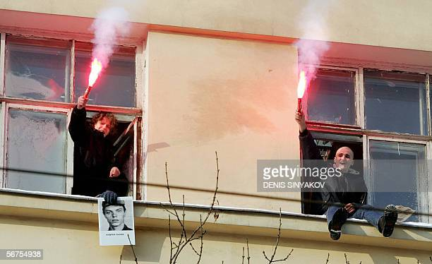 Members of the radical National Bolshevik party light flares holding a portrait of the private Andrei Sychev who was forced to crouch for hours and...