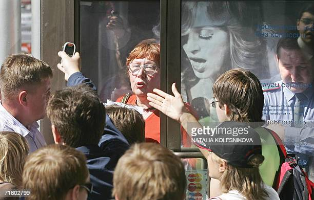 Moscow, RUSSIAN FEDERATION: People gestures as they stand in a queue to buy tickets for pop star Madonna's performance in central Moscow, 08 August...