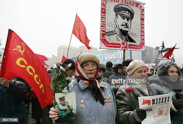 Russian Communist party supporters carrying red flags and portraits gather to pay respect to the grave of the Soviet dictator Joseph Stalin on the...