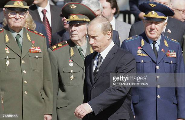 Russian President Vladimir Putin passes by high ranked WWII veterans during the wreath laying ceremony at the Tomb of the Unknown Soldier in front of...
