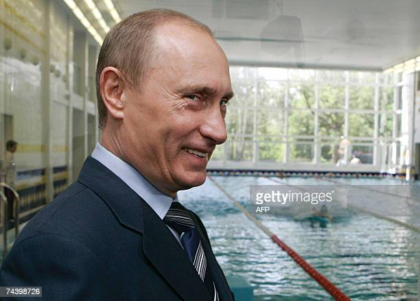 Russian President Vladimir Putin smiles near a swimming pool as he visits to Moscow's experimental district of Kurkino 05 June 2007 AFP PHOTO / RIA...