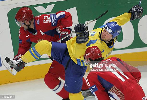 Russians Andrey Markov and Evgeni Malkin send Ukrainian Vasyl Bobrovnikov down during the preliminary round group D game of the IIHF Internetional...