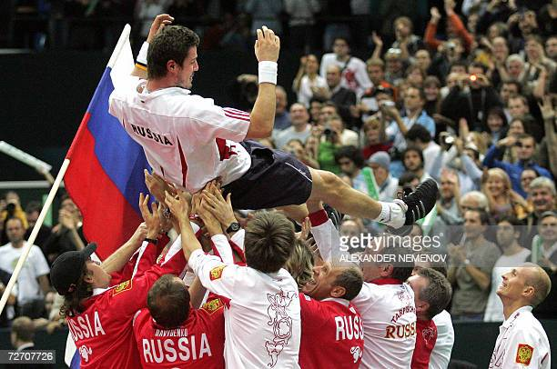 Russia's tennis players throw up Marat Safin as they jubilate his victory over Argentinian Jose Acasuso during the final match of the Davis Cup...